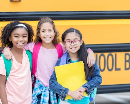Elementary age female friends in front of school bus