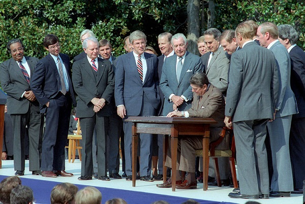 President Reagan signs TRA 1986. Image via Reagan Library.